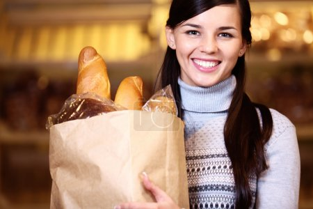 Photo for Image of pretty woman with pack of bread looking at camera - Royalty Free Image