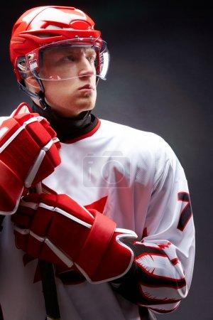 Photo pour Portrait de sportif en uniforme de hockey sur fond noir - image libre de droit