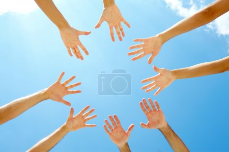 Photo pour Cercle des mains contre le ciel bleu - image libre de droit