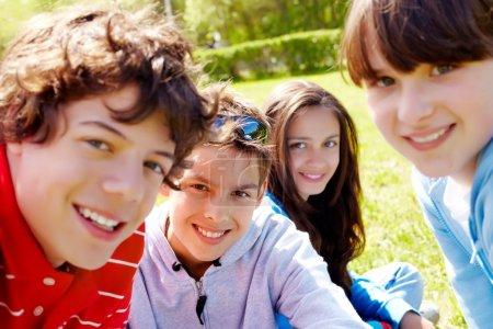 Photo pour Portrait des ados heureux en regardant la caméra dans le parc à été - image libre de droit