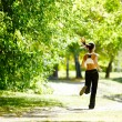 A young girl jogging in the park along trees...