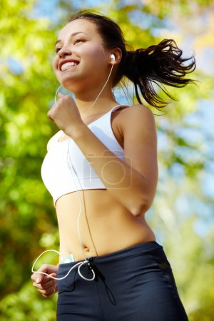 Photo for Portrait of a young woman jogging with a walkman - Royalty Free Image