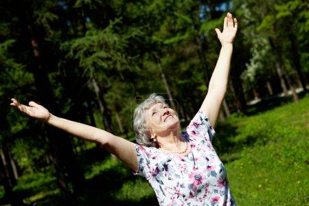 Photo pour Portrait de femme âgée avec ses bras levés à la louange - image libre de droit