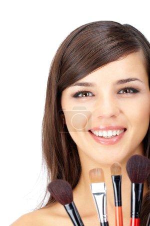 Photo pour Portrait d'une femme avec maquillage et plusieurs pinceaux de maquillage - image libre de droit