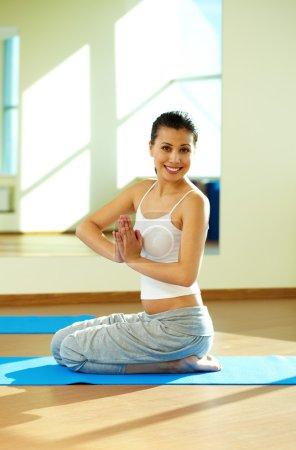 Photo pour Portrait de fille heureuse pratiquant le yoga dans la salle de gym - image libre de droit