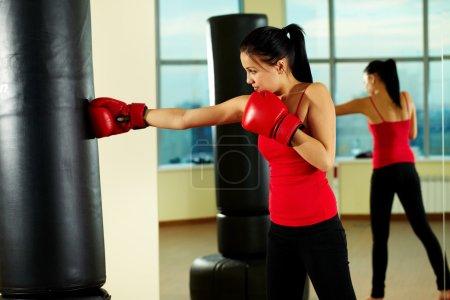 Photo pour Portrait de jeune femme en gants de boxe rouge s'entraînant au gymnase - image libre de droit