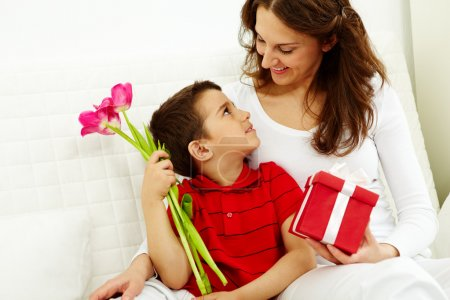 Photo for Cute lad with bunch of beautiful tulips looking at his mother with giftbox - Royalty Free Image