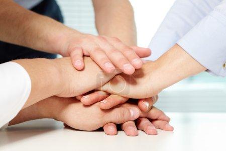 Photo pour Image de l'entreprise les mains sur le dessus de l'autre qui symbolisent le soutien et la puissance - image libre de droit