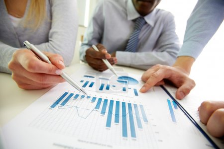 Photo for Business discussing the charts and graphs showing the results of their successful teamwork - Royalty Free Image