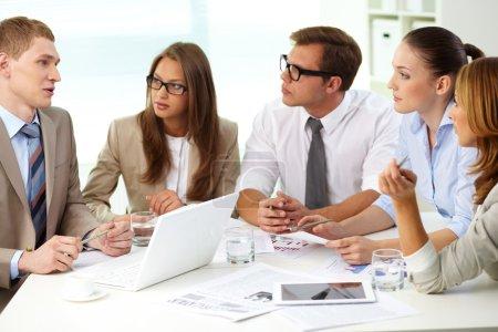 Photo pour Image d'une écoute sérieuse du jeune homme d'affaires lors d'une réunion - image libre de droit