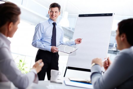 Photo for Cheerful office worker pointing at the blank whiteboard making a presentation - Royalty Free Image