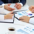 Close-up of business group analyzing financial pap...