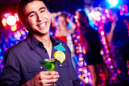 Photo pour Image d'un gars heureux tenant un cocktail à la fête - image libre de droit