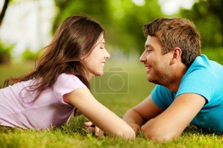 Photo pour Belle Saint-Valentin, couché sur l'herbe, face à face et souriant à l'autre - image libre de droit