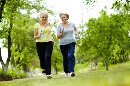 Photo for Portrait of two senior females running outdoors - Royalty Free Image