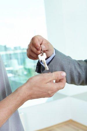 Photo pour Agence immobilière en passant la clé à la maison pour un propriétaire satisfait mâle - image libre de droit