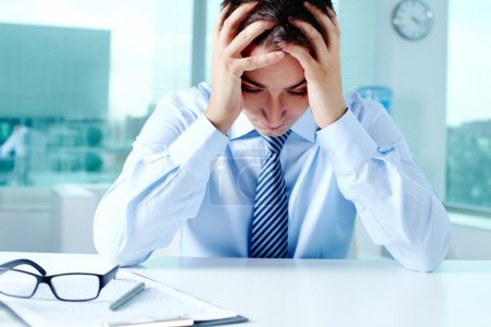 Photo for Stressed businessman sitting at workplace and touching his head - Royalty Free Image