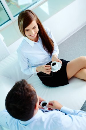 Photo for Photo of friendly business partners talking while drinking coffee in office - Royalty Free Image