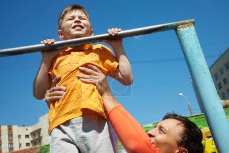 Photo pour Un gamin fait des remontées, son père l'aide. - image libre de droit
