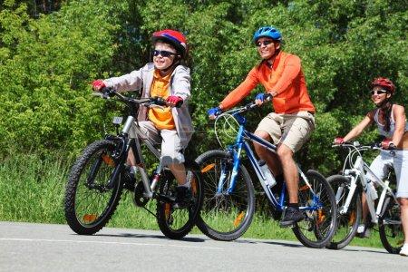 Photo pour Image dynamique d'une famille du vélo dans le parc - image libre de droit