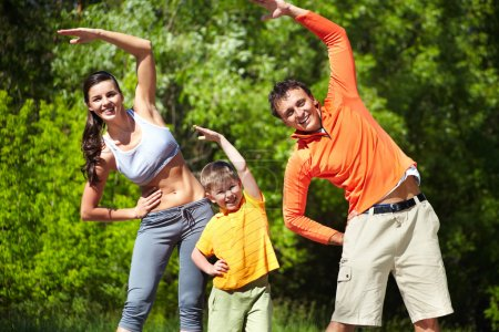 Photo for Portrait of family of three doing physical exercise in park - Royalty Free Image