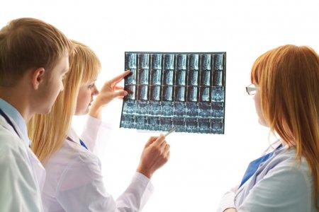 Photo pour Portrait d'un jeune médecin montrant et interprétant une radiographie à ses collègues - image libre de droit