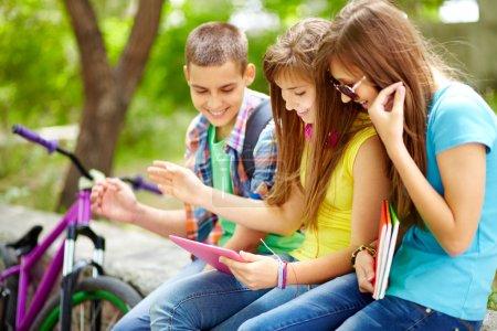 Photo pour Étudiants à traîner ensemble regarder drôle personnel sur l'écran de l'ordinateur tablette - image libre de droit