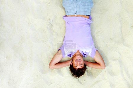 Photo pour Au-dessus d'angle du bel adolescent allongé sur le sable et le rire - image libre de droit