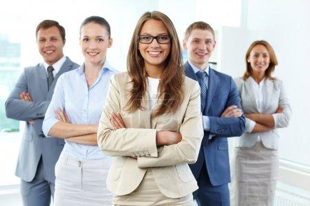 Photo pour Portrait de cinq hommes d'affaires regardant la caméra avec une femme leader devant - image libre de droit