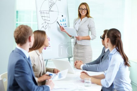 Photo for Confident businesswoman explaining something to colleagues at meeting - Royalty Free Image