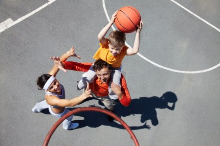 Photo for Image of sporty couple and their son playing basketball - Royalty Free Image