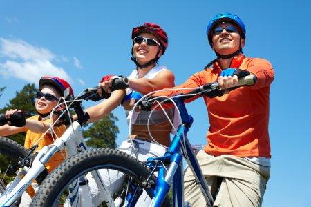 Photo pour Portrait de famille heureuse sur des vélos contre le ciel bleu - image libre de droit