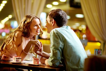Photo for A young happy woman and her boyfriend looking at one another in restaurant - Royalty Free Image