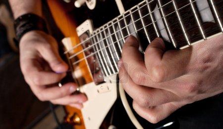 Photo pour Vue rapprochée des mains jouant de la guitare électrique - image libre de droit