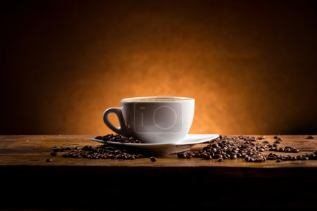 Photo for Cup of coffee on a wooden table on dark background - Royalty Free Image