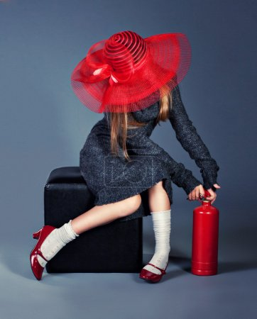 Fashion girl with fire extinguisher in big red hat and red shoes