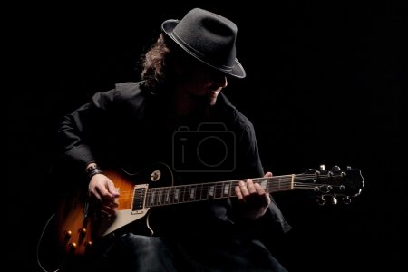 Photo for A man playing eletctric guitar in black clothes - Royalty Free Image