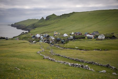 Photo for Houses and stone wall in the village of the Island Mykines, Faroe Islands - Royalty Free Image