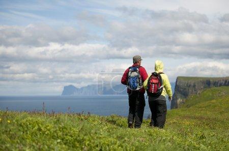 Couple hiking on Mykines, Faroe Islands