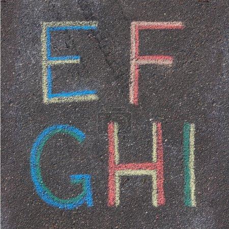 Alphabet letters drawn on asphalt with chalk, e, f, g, h, i