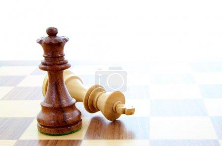 Photo pour Deux pièces d'échecs en bois seuls sur un échiquier. - image libre de droit