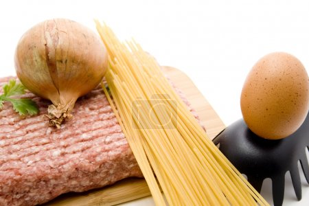 Photo for Minced meat raw with egg, spaghetti and onion on edge board - Royalty Free Image