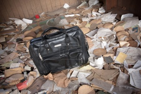 Photo pour Porte-documents noir assis dans une pièce avec des ordures éparpillées . - image libre de droit