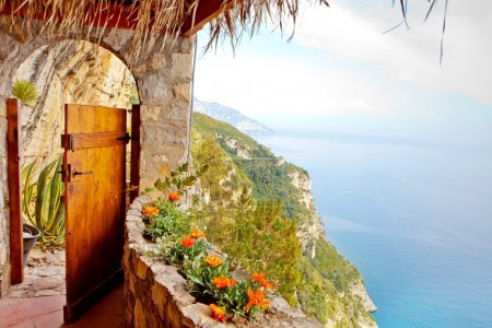 Photo for A wooden door leading to a path along a steep cliff on the Mediterranian Sea - Royalty Free Image