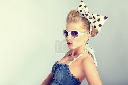 Photo pour Belle jeune femme au maquillage épinglé et coiffure posant en studio. - image libre de droit