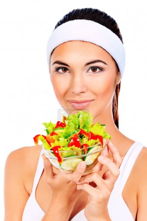 Photo for Portrait of a beautiful young woman eating vegetable salad. Isolated over white background. - Royalty Free Image