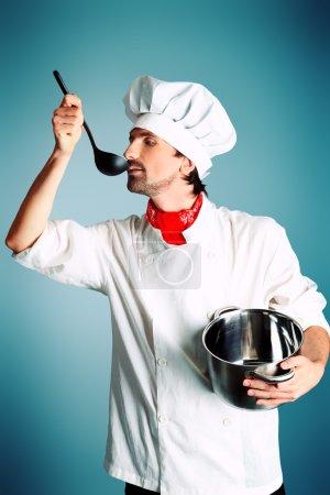 Photo pour Portrait d'un cuisinier tenant une casserole et une louche. Tourné dans un studio . - image libre de droit
