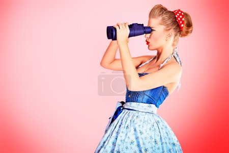 Photo for Beautiful young woman with pin-up make-up and hairstyle looking through binoculars. - Royalty Free Image