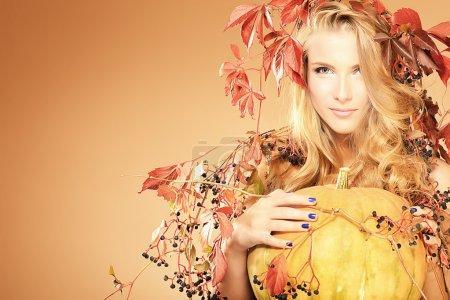 Portrait of a beautiful autumn woman with pumpkin.