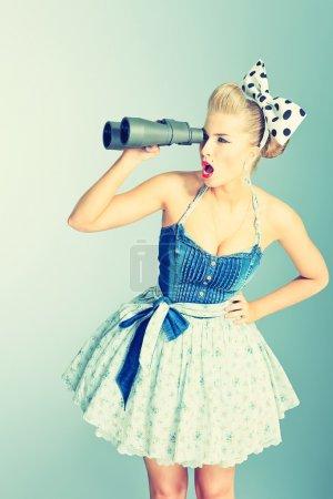 Photo pour Belle jeune femme avec pin up maquillage et coiffure en regardant à travers les jumelles. - image libre de droit